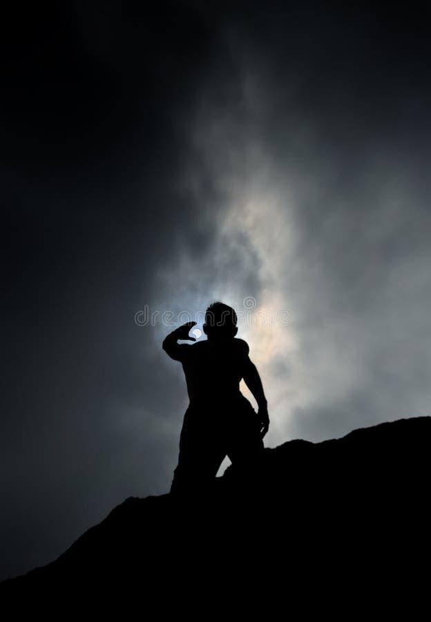 Silhouet die van de Mens zich op Rots bevinden die tot de Hemel tijdens Gedeeltelijke Verduistering bereiken stock foto