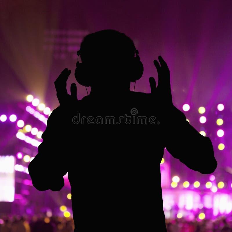 Silhouet die van DJ hoofdtelefoons dragen en bij een nachtclub presteren royalty-vrije stock afbeelding