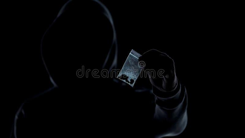 Silhouet die van drugdealer pakket met marihuana tonen bij camera, verslaving royalty-vrije stock afbeeldingen