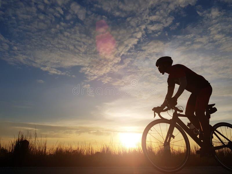 Silhouet die van fietser een wegfiets berijden op open weg in avond tijdens zonsondergang Sporten en openluchtactiviteitenconcept stock afbeeldingen