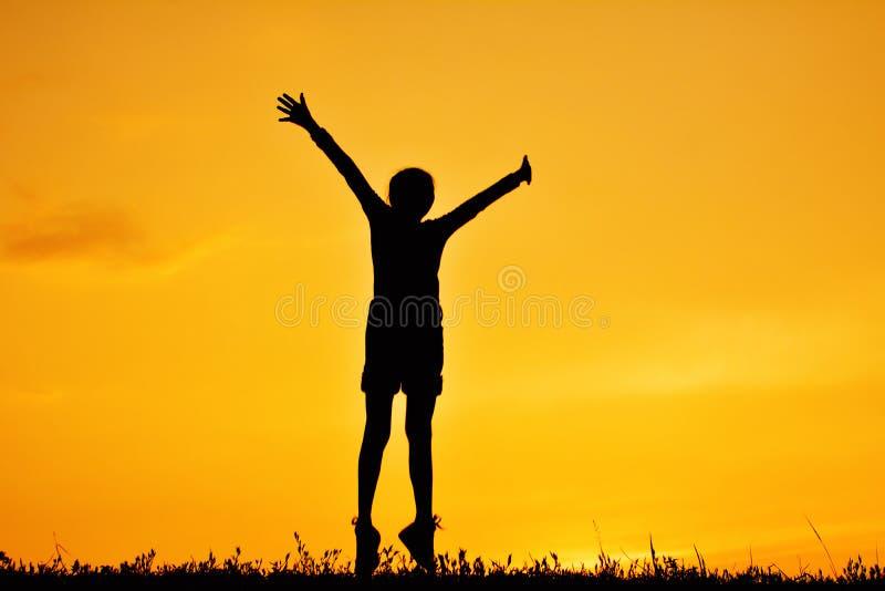 Silhouet die van gelukkig meisje zich op grasgebied bevinden royalty-vrije stock afbeeldingen