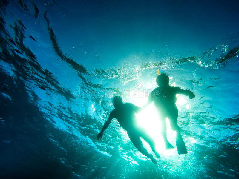 Silhouet die van hoger paar samen in tropische overzees zwemmen royalty-vrije stock foto's