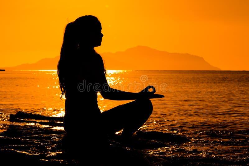 Silhouet die van jong meisje op het overzees mediteren royalty-vrije stock foto's