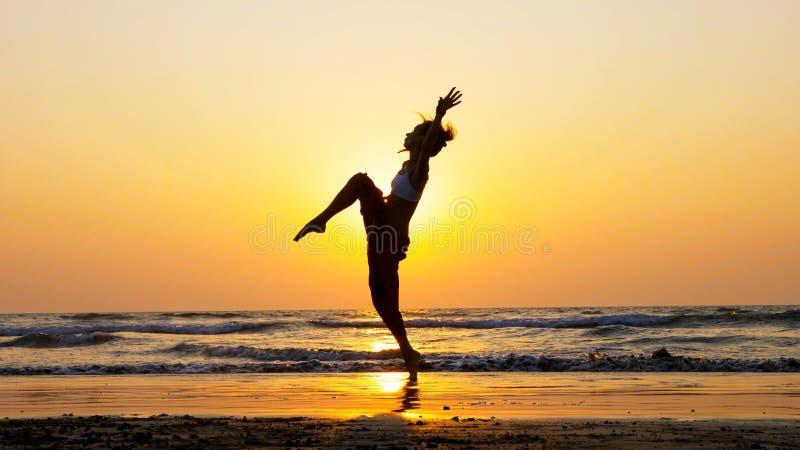 Silhouet die van jong meisje op het strand bij zonsondergang dansen royalty-vrije stock afbeeldingen