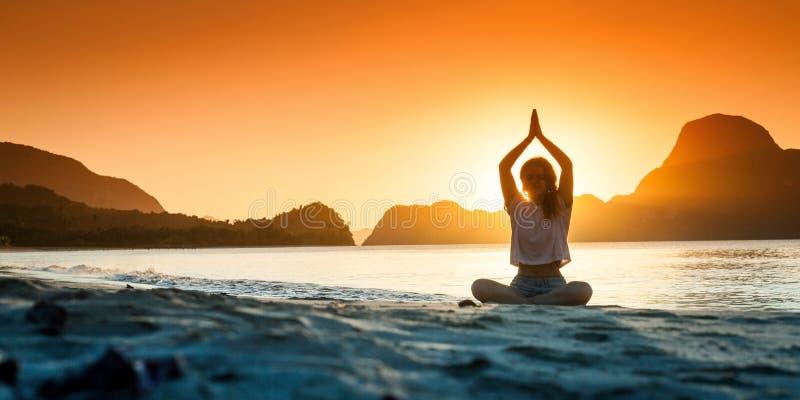 Silhouet die van jong meisje yoga doen in zonsondergangtijd stock afbeelding