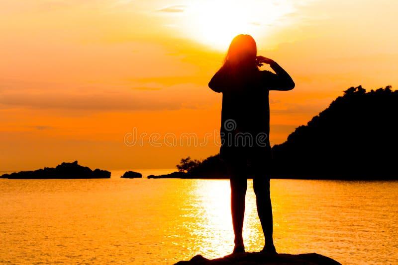 Silhouet die van jonge vrouw het bevinden zich bij ontspant stelt of de vrijheid stelt of de kou stelt royalty-vrije stock afbeelding