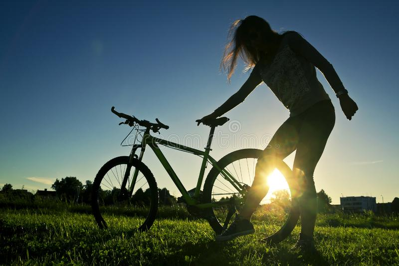 Silhouet die van jonge vrouw zich dichtbij haar fiets bevinden stock afbeeldingen