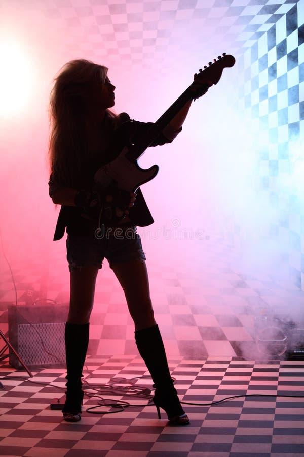 Silhouet die van meisje en elektrische gitaar bevinden zich spelen stock foto's