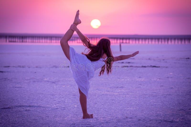 Silhouet die van meisje oefeningen op het zoute meer doen bij zonsondergang royalty-vrije stock afbeelding