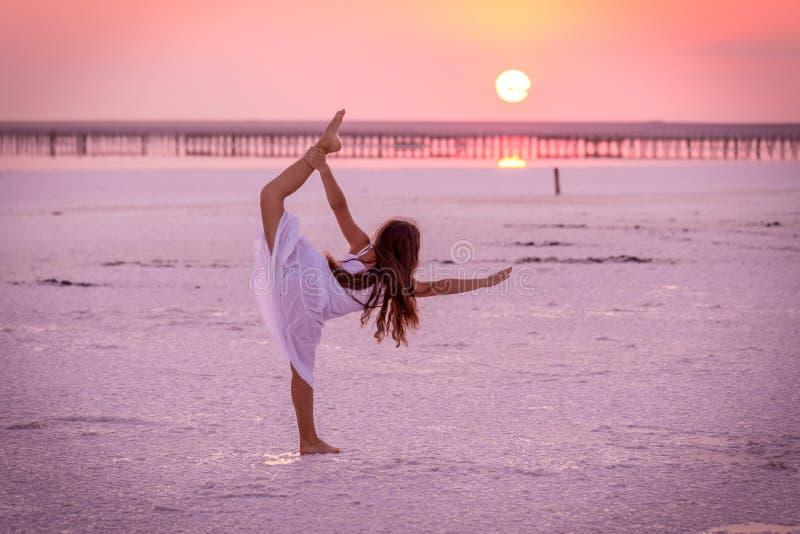 Silhouet die van meisje oefeningen op het zoute meer doen bij zonsondergang stock afbeeldingen