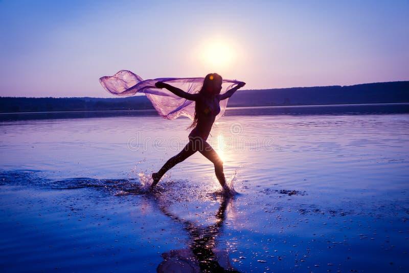 Silhouet die van meisje op het strand lopen royalty-vrije stock afbeelding