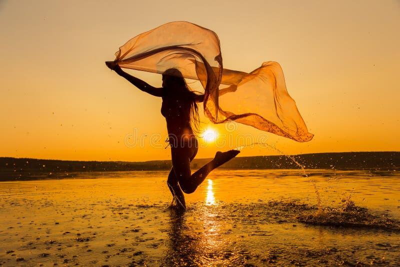 Silhouet die van meisje op het strand lopen royalty-vrije stock foto's