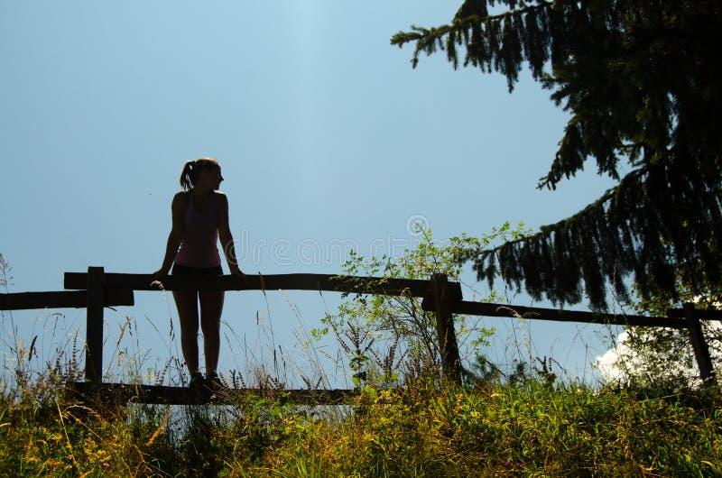 Silhouet die van meisje zich op de houten omheining bevinden stock foto's