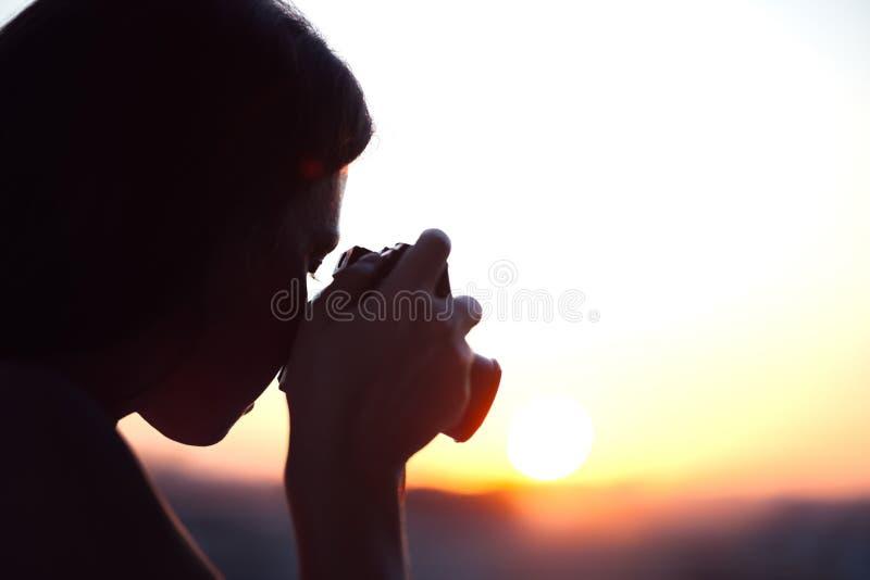 Silhouet die van meisjesfotograaf beeld het plaatsen zon op compacte camera nemen De achtergrond van de zonsondergang royalty-vrije stock afbeelding