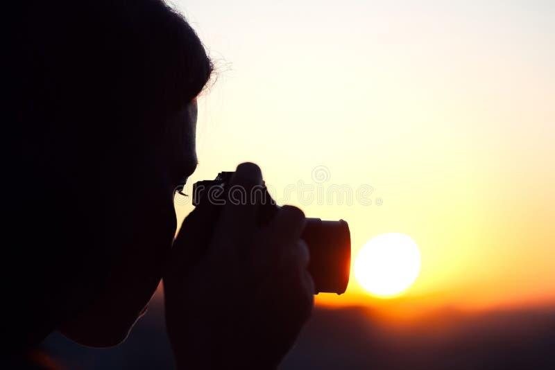 Silhouet die van meisjesfotograaf beeld het plaatsen zon op compacte camera nemen De achtergrond van de zonsondergang stock fotografie