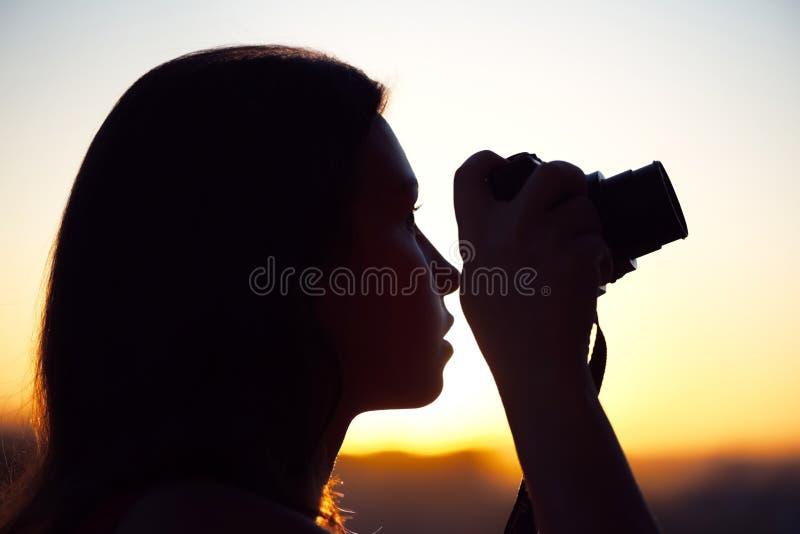 Silhouet die van meisjesfotograaf beeld het plaatsen zon op compacte camera nemen De achtergrond van de zonsondergang royalty-vrije stock foto's