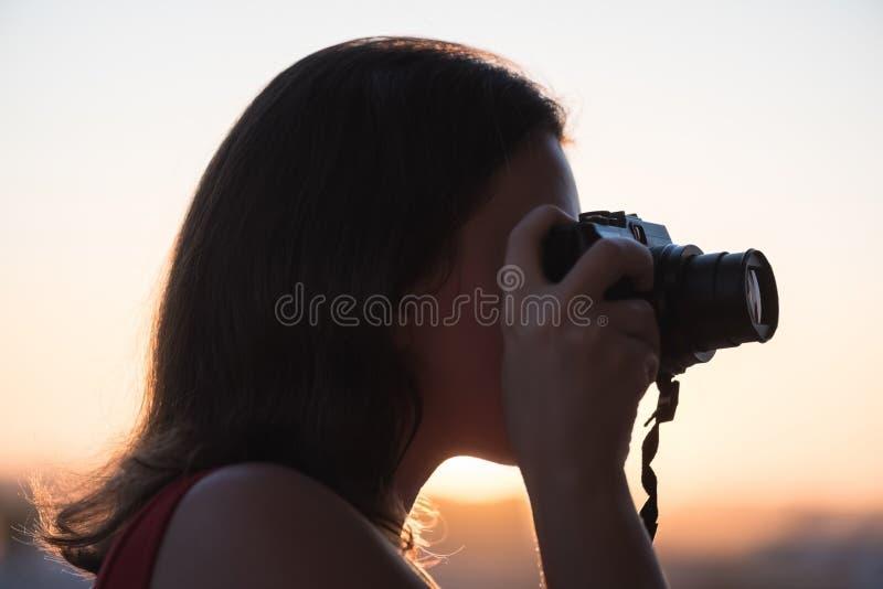 Silhouet die van meisjesfotograaf beeld het plaatsen zon op compacte camera nemen De achtergrond van de zonsondergang stock afbeeldingen