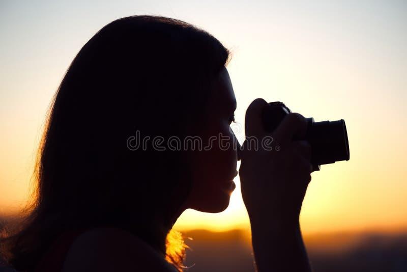 Silhouet die van meisjesfotograaf beeld het plaatsen zon op compacte camera nemen De achtergrond van de zonsondergang royalty-vrije stock fotografie