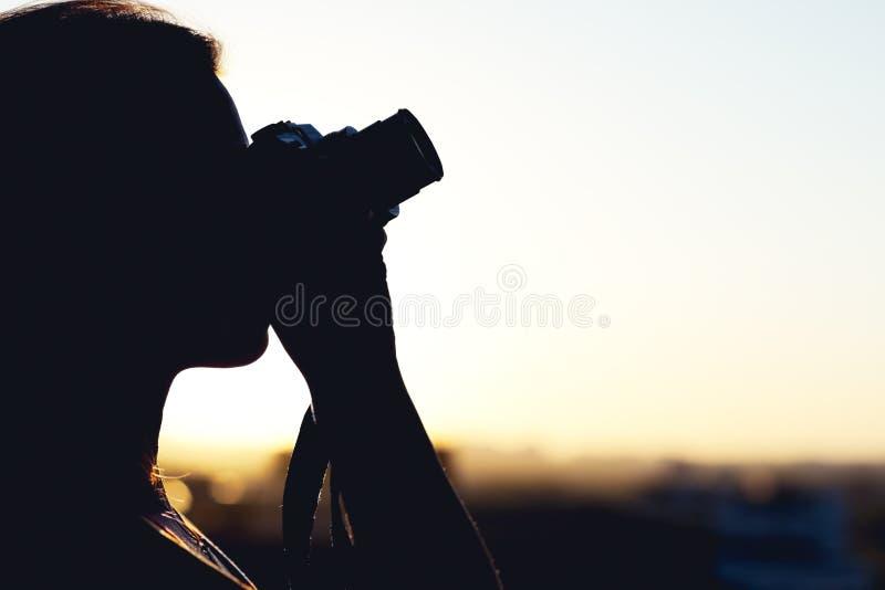 Silhouet die van meisjesfotograaf beeld het plaatsen zon op compacte camera nemen De achtergrond van de zonsondergang royalty-vrije stock afbeeldingen