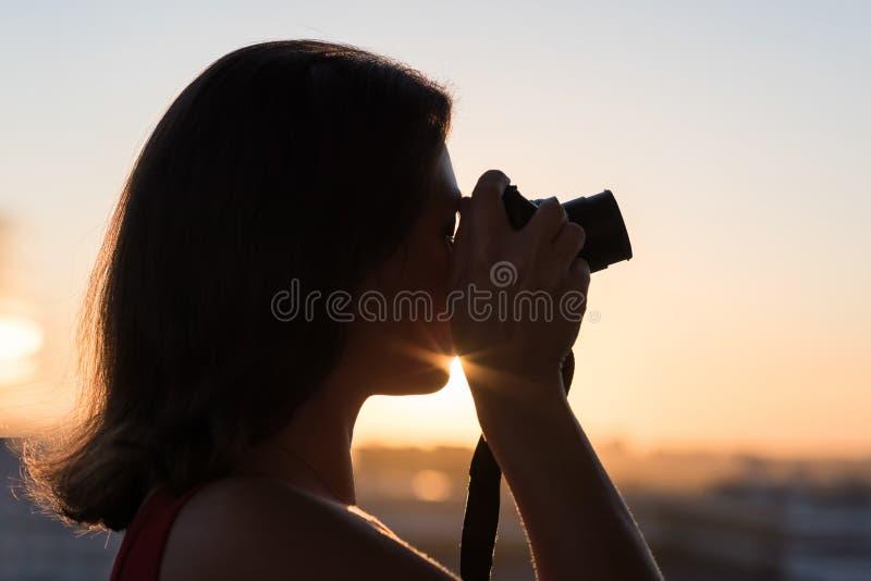 Silhouet die van meisjesfotograaf beeld het plaatsen zon op compacte camera nemen De achtergrond van de zonsondergang royalty-vrije stock foto