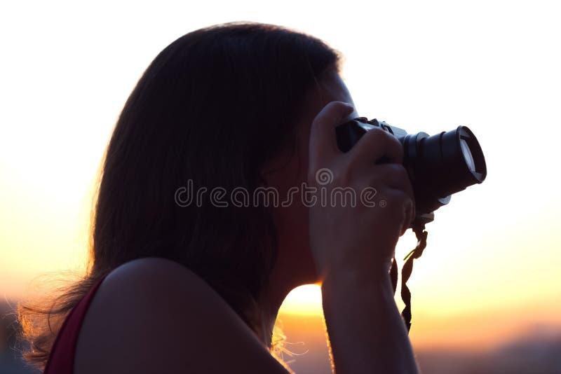 Silhouet die van meisjesfotograaf beeld het plaatsen zon op compacte camera nemen De achtergrond van de zonsondergang stock foto's