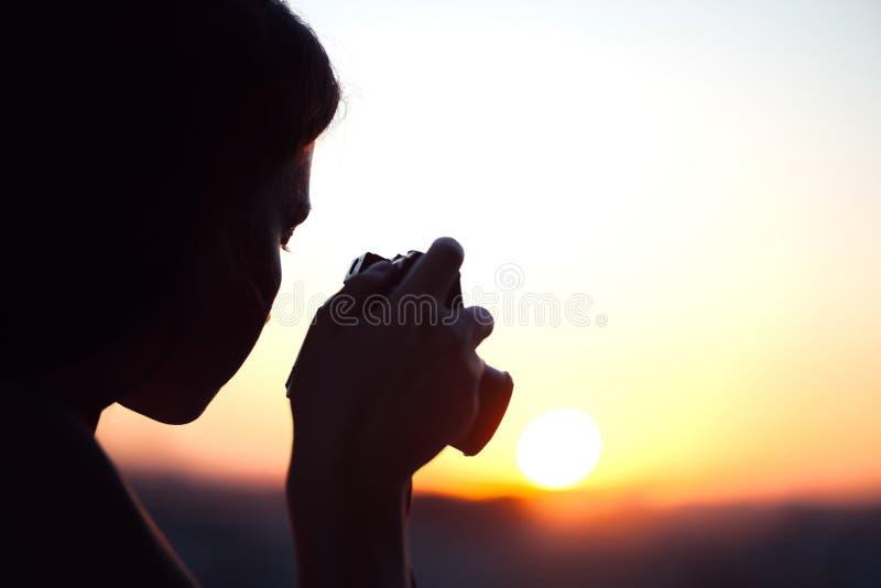Silhouet die van meisjesfotograaf beeld het plaatsen zon op compacte camera nemen De achtergrond van de zonsondergang stock foto