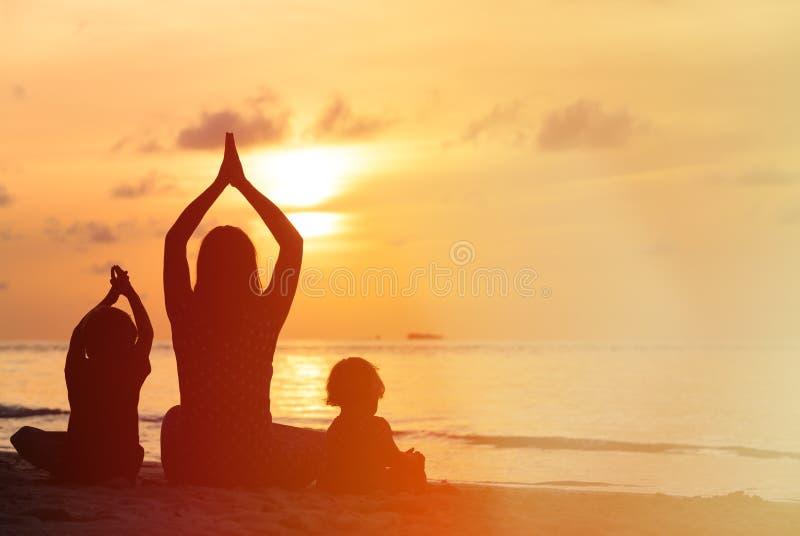 Silhouet die van moeder en jonge geitjes yoga doen bij zonsondergang stock afbeelding
