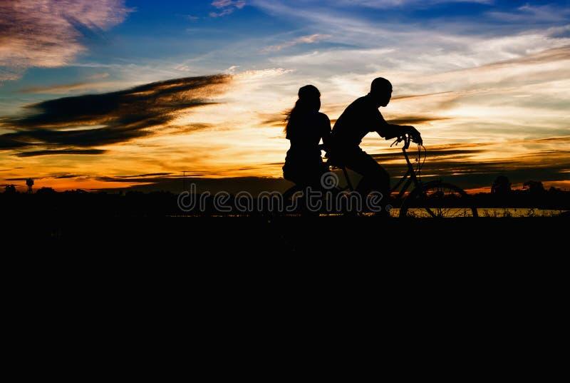 Silhouet die van Paar een fiets berijden bij zonsondergang stock foto's