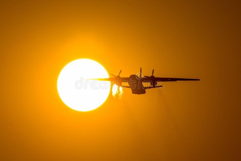 Silhouet die van schroefturbinevliegtuig tijdens zonsondergang, vliegenvleugel door de schijf van de zon opstijgen Een sleep van  royalty-vrije stock afbeeldingen