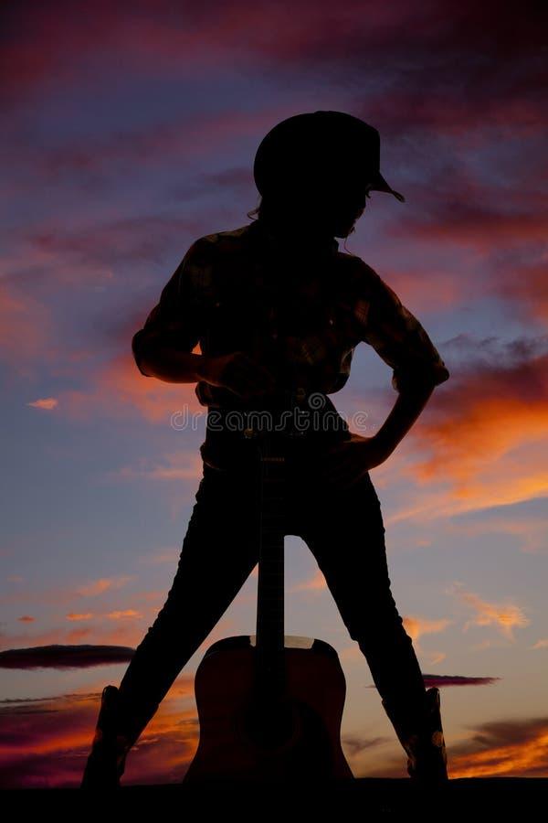 Silhouet die van veedrijfster zich met een gitaar tussen haar benen bevinden royalty-vrije stock fotografie