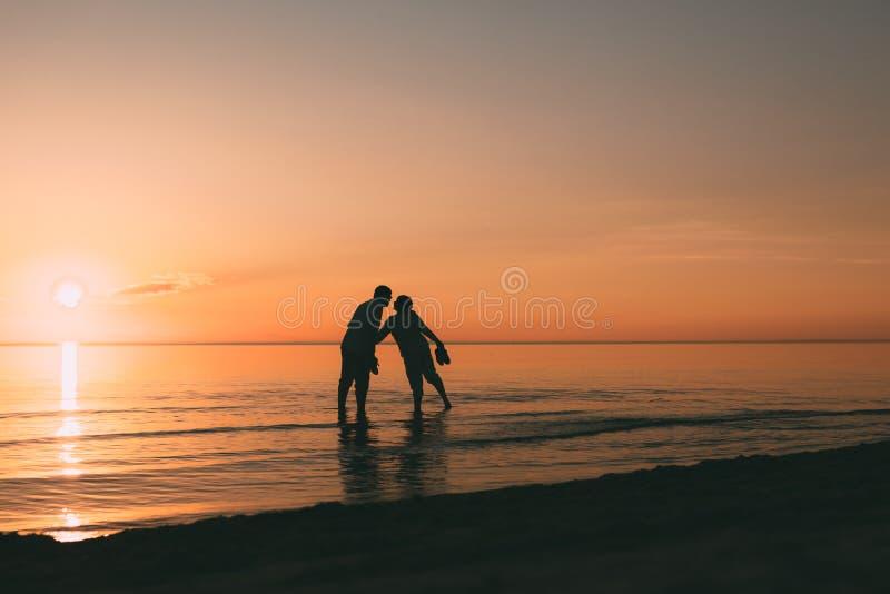 Silhouet die van volwassen paar zich in water het bevinden wil kussen stock foto's