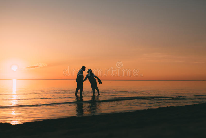 Silhouet die van volwassen paar zich in water het bevinden wil kussen royalty-vrije stock fotografie