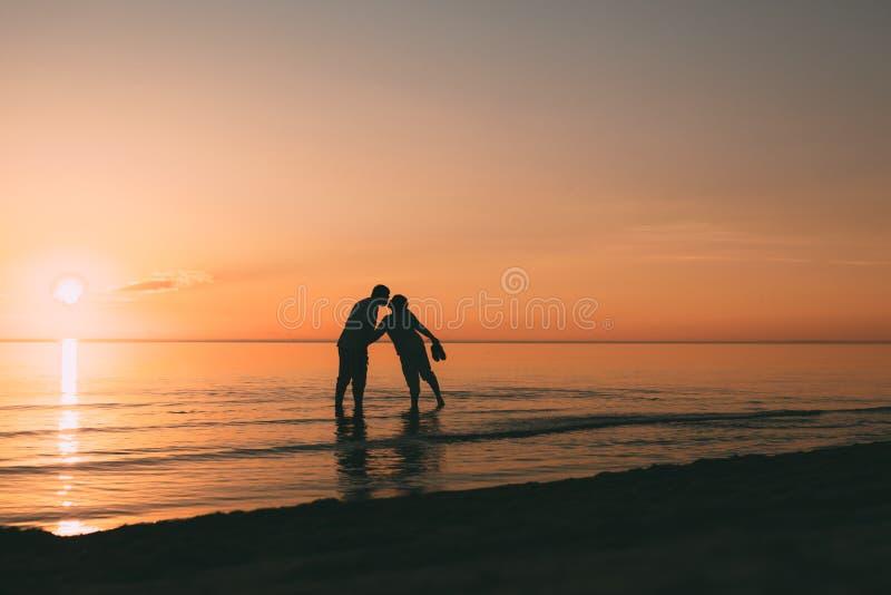 Silhouet die van volwassen paar zich in water het bevinden wil kussen royalty-vrije stock afbeeldingen