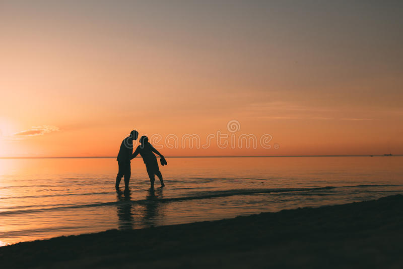 Silhouet die van volwassen paar zich in water het bevinden wil kussen royalty-vrije stock foto