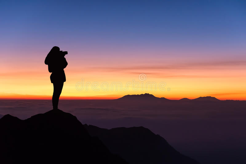 Silhouet die van vrouw foto op de bovenkant van berg nemen en stock afbeeldingen