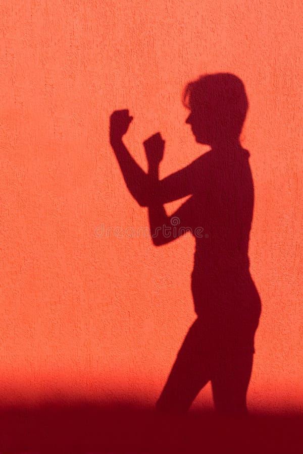 Silhouet die van vrouw vuisten op rode muur tonen royalty-vrije stock foto
