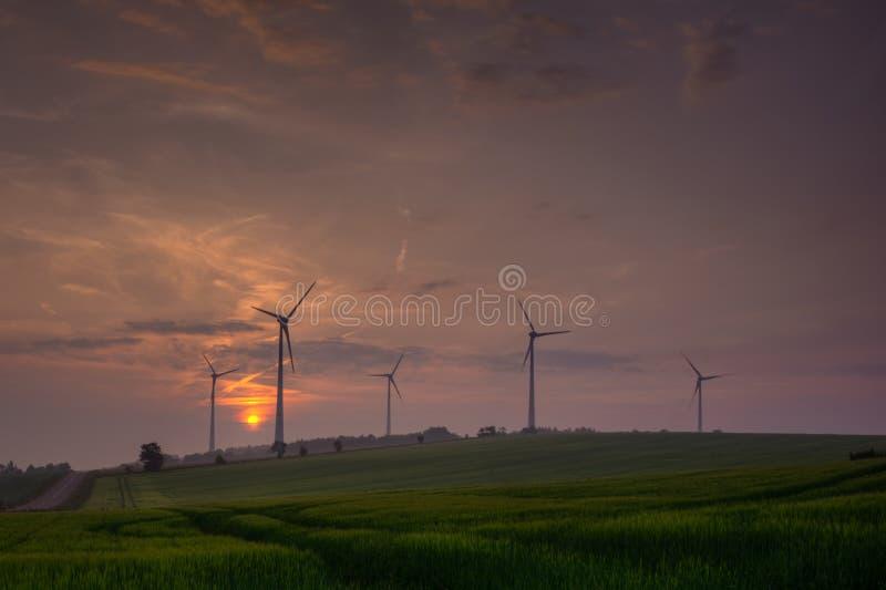 Silhouet die van windturbine elektriciteit op zonsondergang produceren royalty-vrije stock foto's