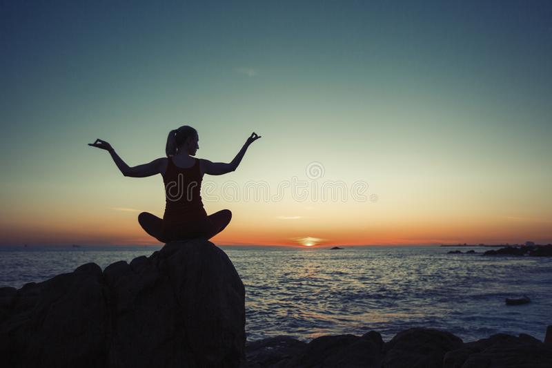 Silhouet die van yogavrouw op de overzeese kust mediteren stock foto