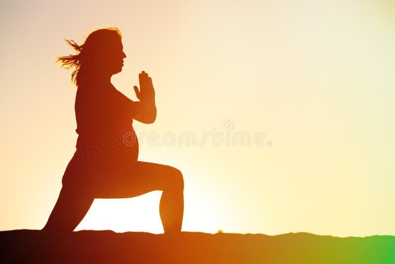 Silhouet die van zwangere vrouw yoga op strand doen royalty-vrije stock foto