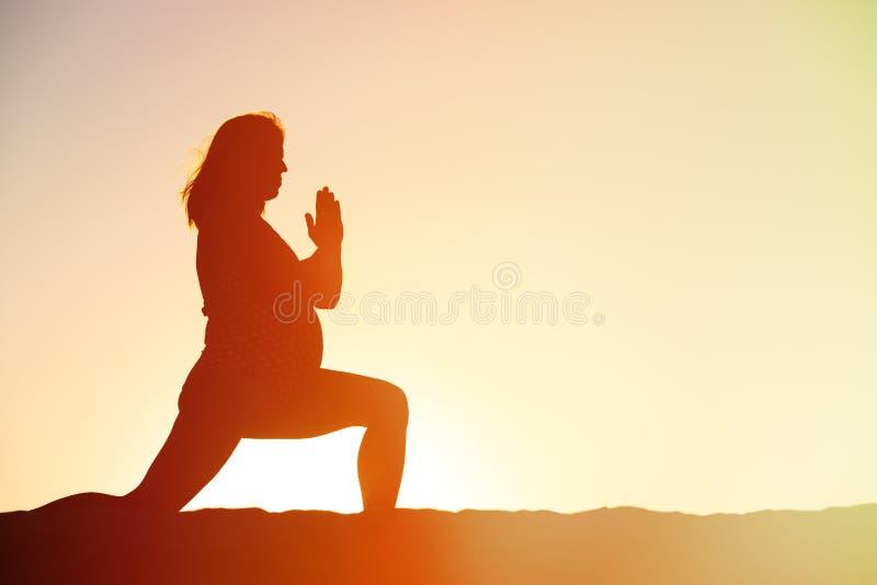 Silhouet die van zwangere vrouw yoga op strand doen stock afbeeldingen