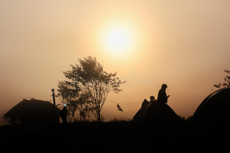 Silhouet donkere mens, hut en boomschaduw in dicht mist in winte stock afbeeldingen