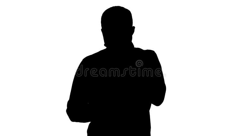 Silhouet Droevige jonge mens die en zijn mobiele telefoon met zijn hand op zijn gezicht lopen bekijken vector illustratie