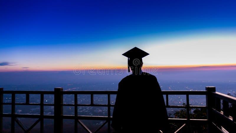 Silhouet een diploma behaalde student die tegen zon bij terras toenemen stock foto