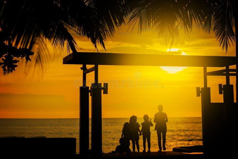 Silhouet, een groep die gelukkige kinderen, de mooie gele overzeese zonsondergang bewonderen Palmbladen Hotel in Thailand De zome royalty-vrije stock afbeeldingen