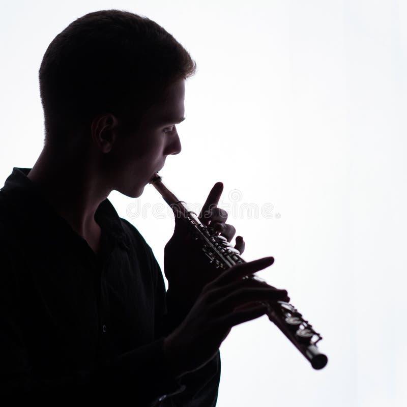 Silhouet Een jonge mens speelt de fluit Een vierkant beeld De ruimte van het exemplaar stock afbeelding
