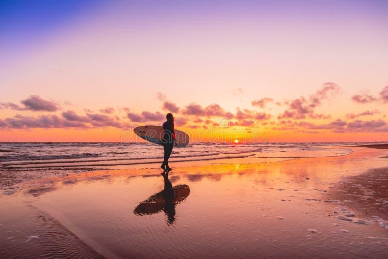 Silhouet en bezinning van surfermeisje met surfplank op een strand bij zonsondergang Surfer en oceaan royalty-vrije stock afbeelding