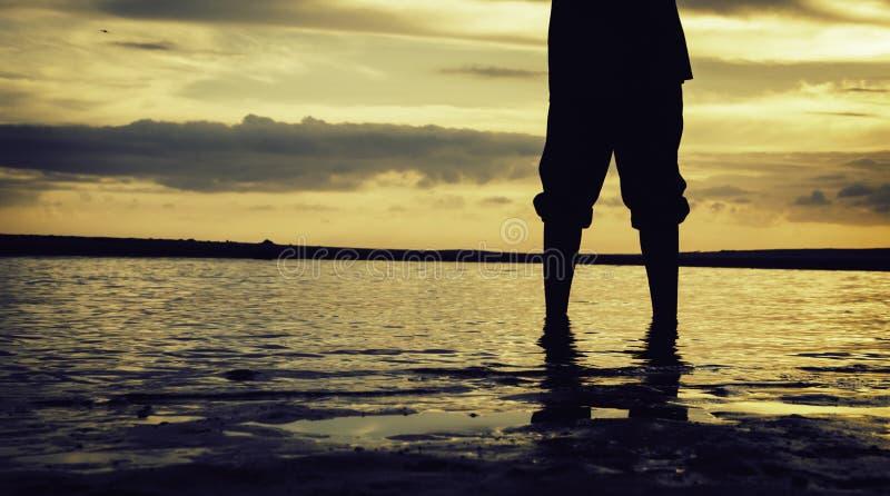 Silhouet en de bebouwde eenzame jongen die van het beeldconcept zich bij zandig strand met mooie zonsopgangzonsondergang bevinden royalty-vrije stock fotografie