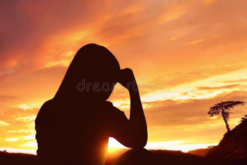Silhouet gedeprimeerde vrouwenzitting alleen bovenop de berg royalty-vrije stock foto's