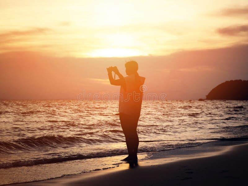 Silhouet glimlachende vrouw die foto op het strand nemen royalty-vrije stock fotografie