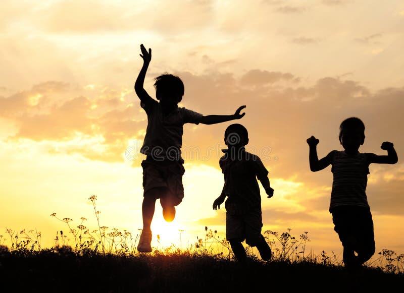 Silhouet, groep gelukkige kinderen stock afbeeldingen